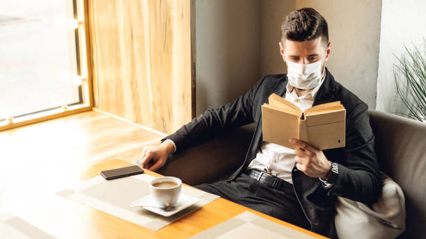 Schöne Erwachsene bärtigen Mann drinnen in Café. Lifestyle-Konzeptfoto mit Kopierraum. Bild mit Buch und schützender Gesichtsmaske – Foto