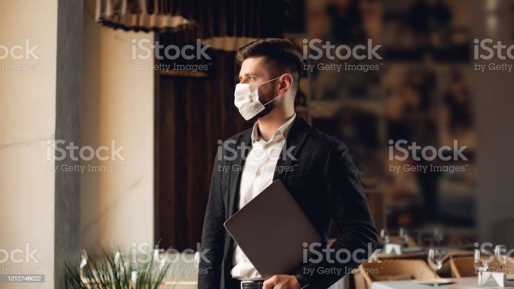Guapo hombre barbudo adulto en el café. Foto de concepto de estilo de vida con espacio de copia. Imagen con portátil gris y máscara protectora en la cara - Foto de stock de Adulto libre de derechos
