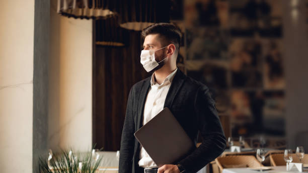 handsome adult bearded man indoors in cafe. lifestyle concept photo with copy space. picture with gray laptop and protective mask on the face - covid restaurant imagens e fotografias de stock