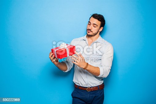 istock handsome adult man on blue background with christmas gift 530222969
