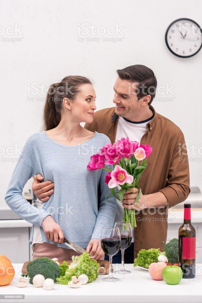 homem adulto bonito apresentando buquê de tulipas para esposa enquanto ela cozinha - foto de acervo