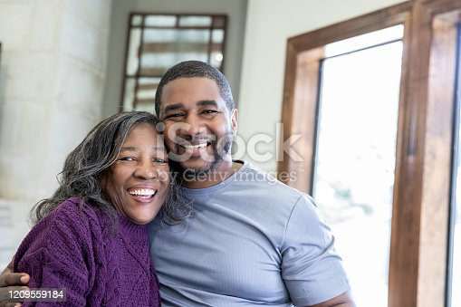 Handsome adult man standing beside senior mother smiling and embracing her
