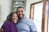 istock Handsome adult man standing beside senior mother smiling and embracing her 1209559184