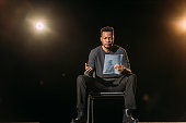 istock handsome african american actor holding scenario on stage during rehearse 1210331584