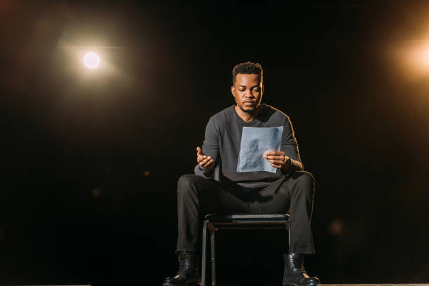 handsome african american actor holding scenario on stage during rehearse stock photo