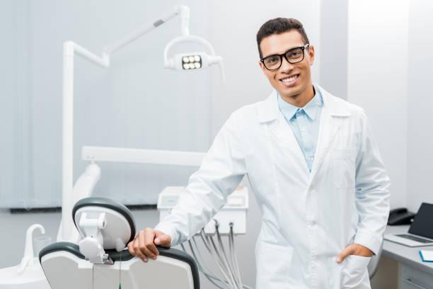 handsome african american dentist smiling and standing with hand in pocket - dentist zdjęcia i obrazy z banku zdjęć