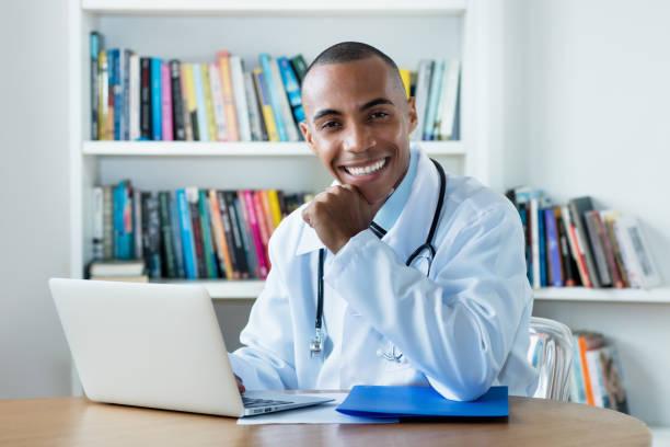 Guapo médico hombre afroamericano en la computadora - foto de stock