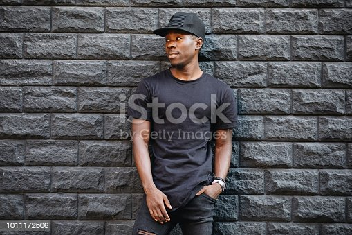 Handsome african american man in blank black t-shirt standing against brick wall