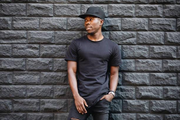 Handsome african american man in blank black t-shirt standing against brick wall – zdjęcie