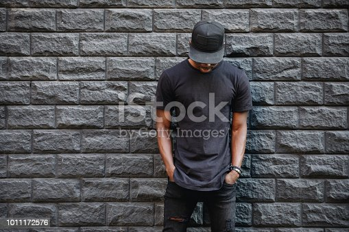 istock Handsome african american man in blank black t-shirt standing against brick wall 1011172576
