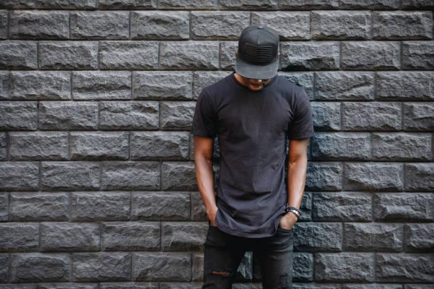 bel homme afro-américain à vide permanent de t-shirt noir contre le mur de briques - mannequin photos et images de collection