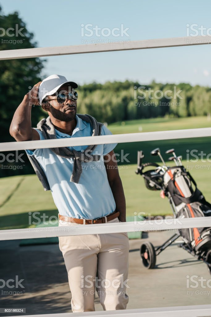 Handsome african american man in cap and sunglasses standing with hand in pocket stock photo