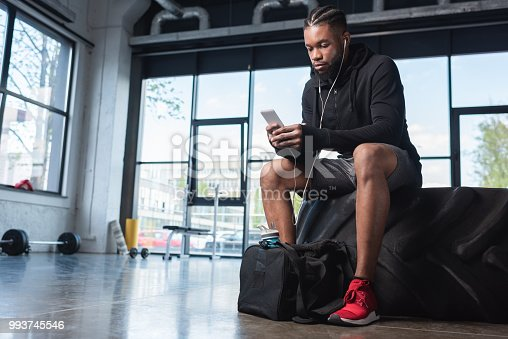 istock handsome african american man in earphones sitting in tyre and using smartphone in gym 993745546