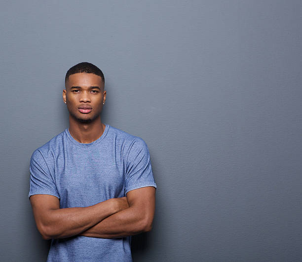 Handsome african american man posing with arms crossed stock photo