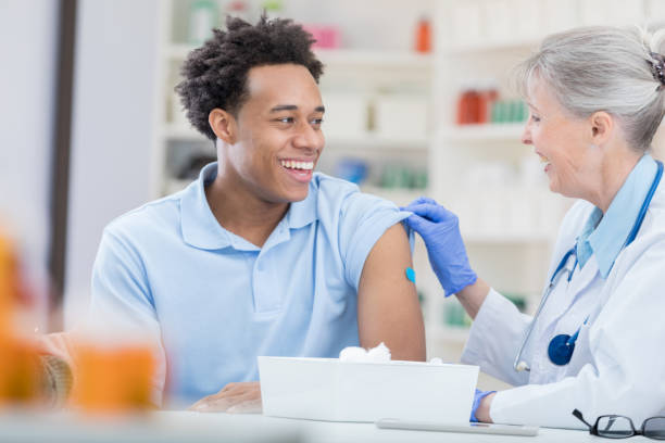 handsome african american man receives flu shot - vaccination stock pictures, royalty-free photos & images