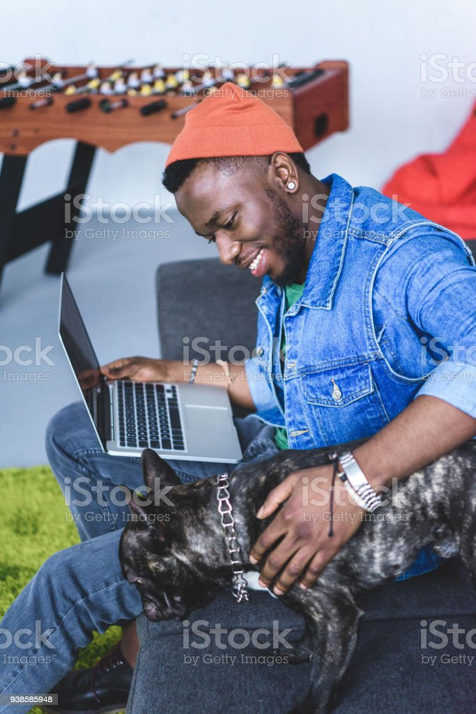 Handsome african american man sitting on sofa with laptop and stroking French bulldog stock photo