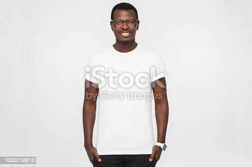 istock Handsome african american man wearing blank white t shirt, smart watches and trendy eyeglasses, isolated on grey background, smiling, standing in hands in pockets pose 1000216810