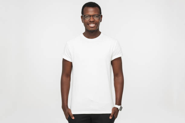 Handsome african american man wearing blank white t shirt, smart watches and trendy eyeglasses, isolated on grey background, smiling, standing in hands in pockets pose Handsome african american man wearing blank white t shirt, smart watches and trendy eyeglasses, isolated on grey background, smiling, standing in hands in pockets pose white t shirt stock pictures, royalty-free photos & images