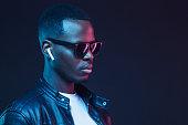 istock Handsome African American man wearing wireless earphones and leather jacket 1125110807