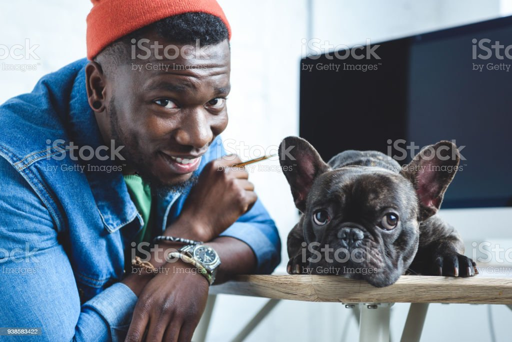 Handsome african american man with Frenchie dog by computer screen stock photo