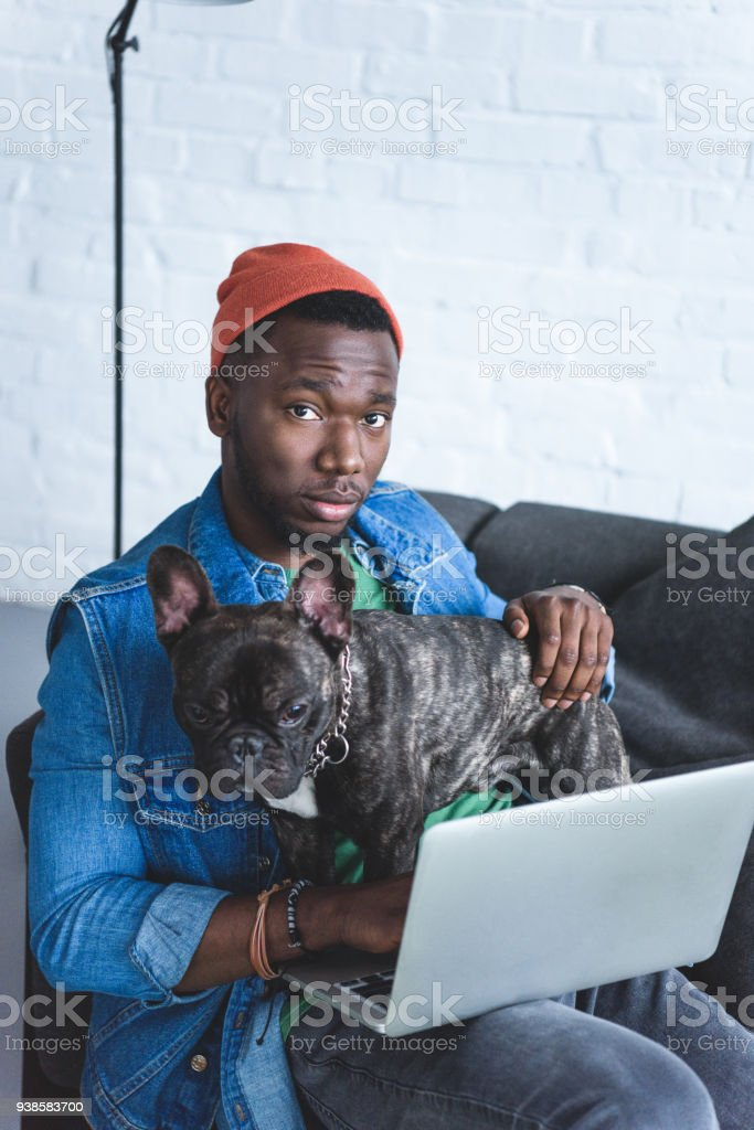 Handsome african american man working on laptop and hugging Frenchie dog stock photo