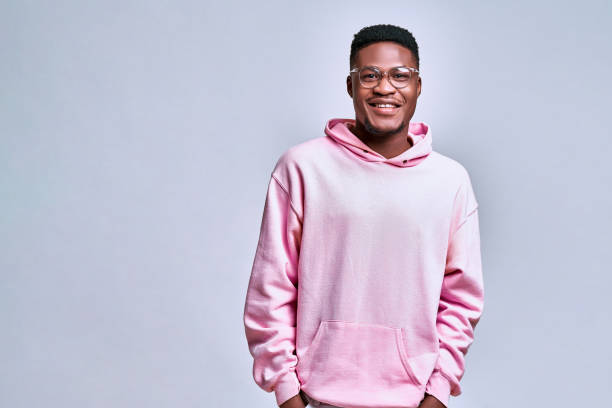 Handsome african american young man in glasses and pink hoodie standing on grey background stock photo