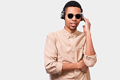 istock Handsome African American young man with headphones listening the favorites music. Afro male student wearing sunglasses and casual outfit, posing over white studio background. 1172152391
