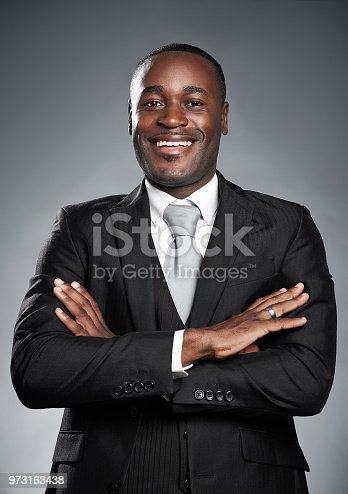 istock Handsome African-American businessman smiles with arms folded 973163438