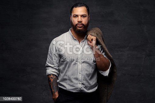 istock Handsome African-American man with a tattoo on his arm, dressed a white shirt, holds a jacket on a shoulder. Isolated on a dark background. 1028400782
