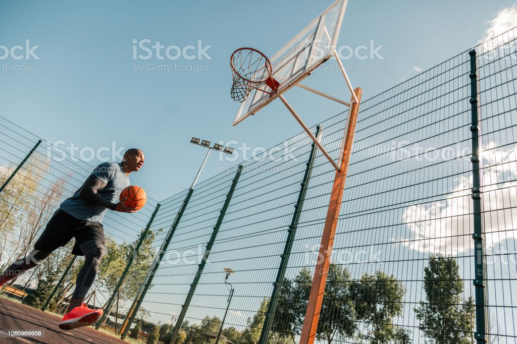 Professional workout. Handsome Afro American man holding a ball while...
