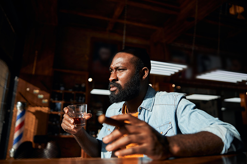 Bearded gentleman looking away with serious expression while holding cigar and glass of alcoholic drink
