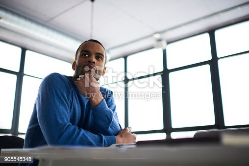 istock Handsome afro american student thinking about creative project sitting near copy space area for advertising, pensive dark skinned businessman pondering on startup problem solution concentrated on idea 905545348