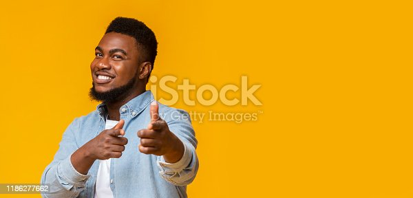 istock Handsome afro guy pointing fingers at camera and smiling 1186277662