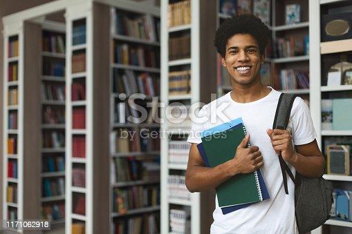 istock Handsome afro student posing on bookshelves background 1171062918