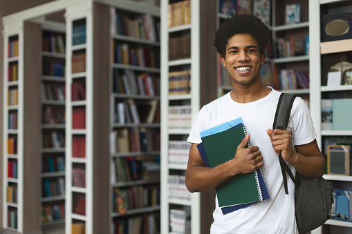 Handsome african american male student posing in campus library, empty space