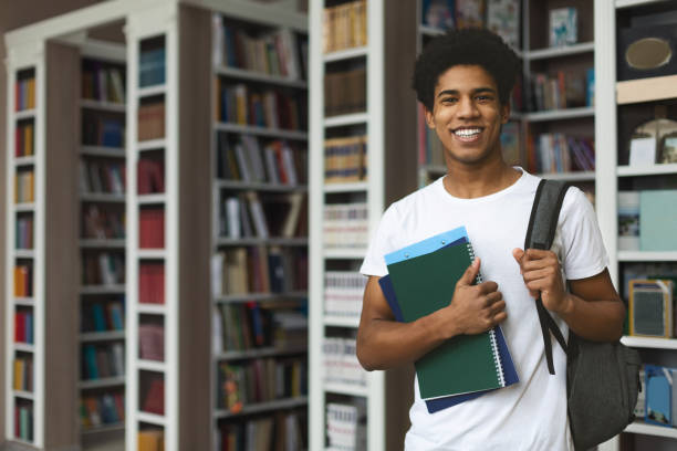 guapo estudiante afro posando en estanterías de fondo - estudiante fotografías e imágenes de stock