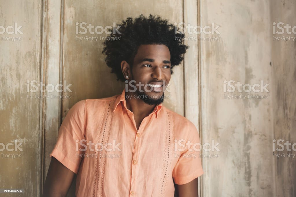 handsome afro-caribbean cuban man leaning on wooden wall stock photo