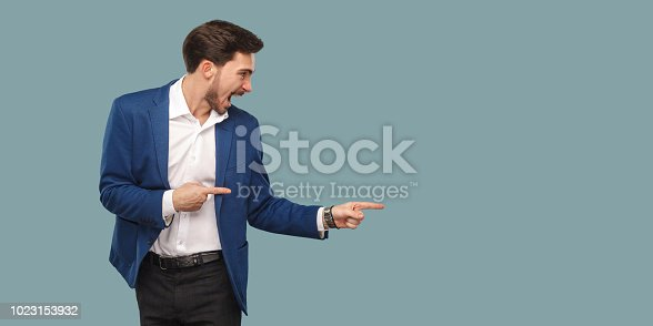 Handsome amazed bearded man in blue suit standing and pointing at background and screaming and looking at copy space. studio, indoor shot isolated on blue background.