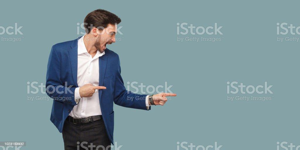 Schöner erstaunt bärtigen Mann im blauen Anzug stehen und deutete auf Hintergrund und schreien und mit Blick auf Textfreiraum. – Foto