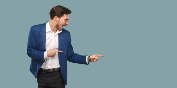 handsome amazed bearded man in blue suit standing and pointing at background and screaming and looking at copy space. - finger point stock photos and pictures