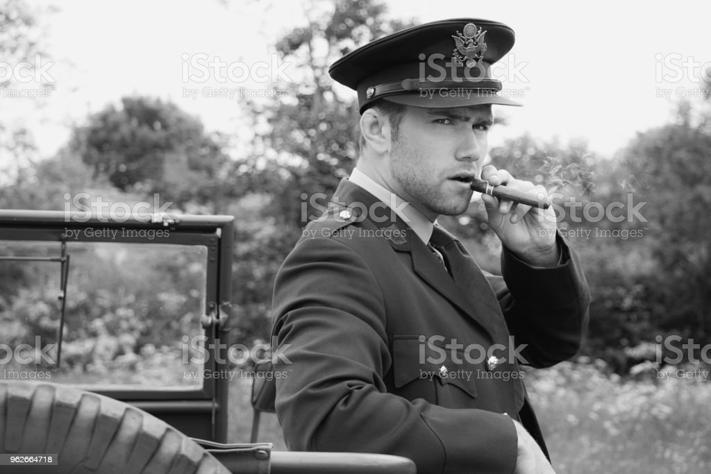 Handsome American WWII GI Army officer in uniform smoking cigar next to Willy Jeep stock photo