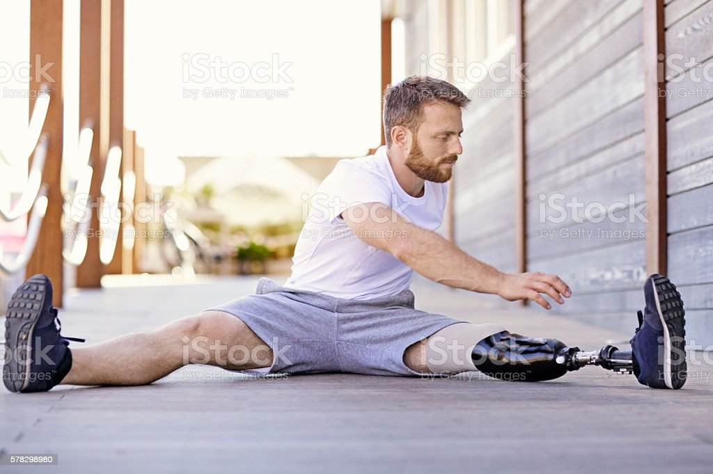 Handsome amputee male working out at summer beach location stock photo