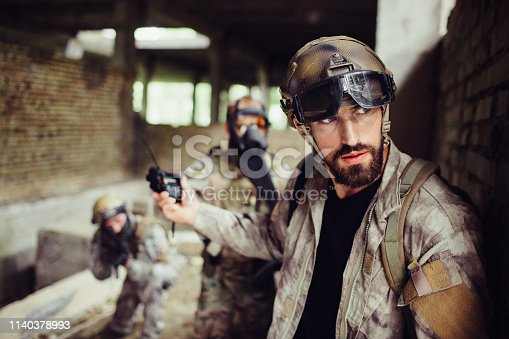 istock Handsome and bearded guy is leaning to wall and looking right. He is careful. Man has stopped his soldiers from attacking. They are waiting. 1140378993