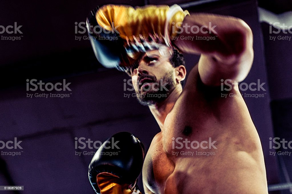 Handsome and Muscular Boxer Guarding Against His Opponent stock photo