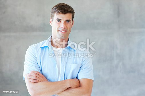 Cropped portrait of a handsome and confident young man standing indoors