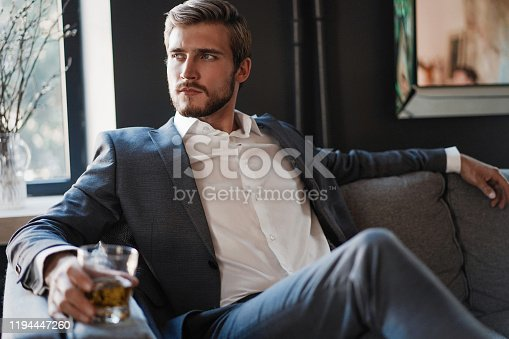 Handsome and successful businessman in stylish suit holding glass whiskey while sitting on the sofa at office