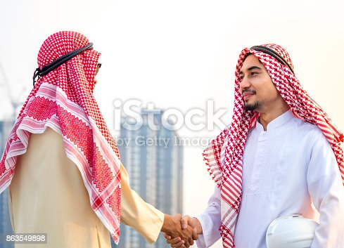 1071990712 istock photo Handsome arab businessman, engineer/architect shaking hands front of building new construction project, togetherness, teamwork, cooperation for business concept 863549898