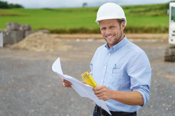 Handsome architect or site supervisor Handsome architect or supervisor standing outdoors on a building site holding a blueprint in his hands looking at the camera with a friendly smile foreman stock pictures, royalty-free photos & images