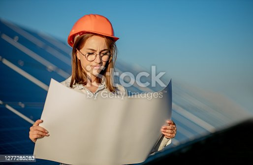 Handsome Architect Woman Examining a Draft Map or Blueprint Project Plan, Worker Activity Looking Out in Photovoltaic Cell Farm or Solar Panels Field.