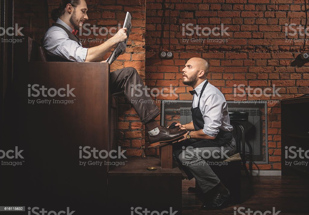 handsome artisan reading while working stock photo